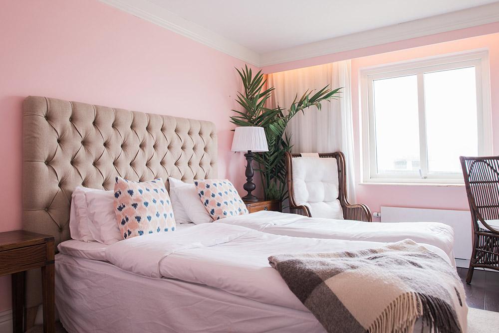 Härlig säng i rosa hotellrum på Falkenberg Strandbad